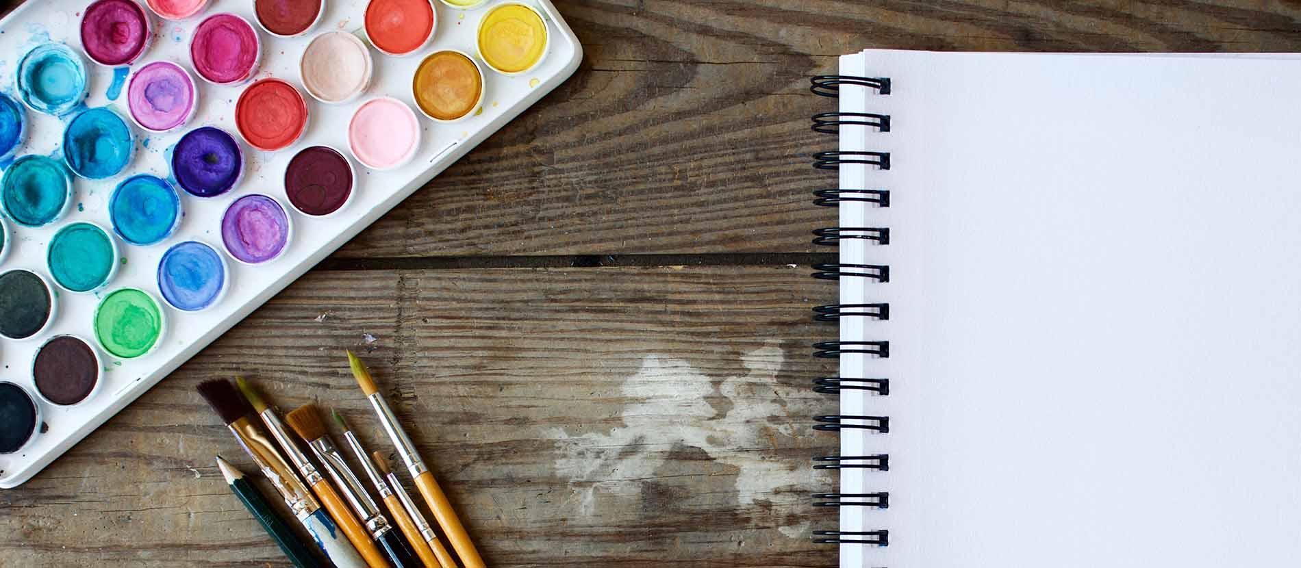 Wassermalfarben, weißer Block und Pinsel auf Holztisch